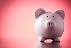 Pink piggy bank on a colorful red background Royalty Free Stock Photography