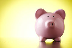 Pink piggy bank on a colorful yellow background Royalty Free Stock Images