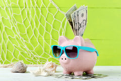 Pink piggy bank. With dollars on white wooden background Royalty Free Stock Image