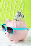 Pink piggy bank. With dollars on white wooden background Stock Images