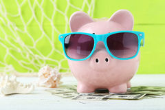 Pink piggy bank. With dollars on white wooden background Royalty Free Stock Images