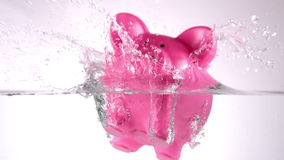 Pink piggy bank falling in water stock video footage