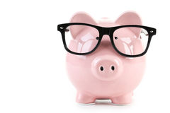 Pink piggy bank. With glasses isolated on a white royalty free stock images