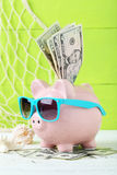 Pink piggy bank. With glasses on white wooden background Stock Photos