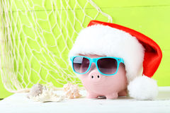 Pink piggy bank. With glasses on white wooden background Royalty Free Stock Image