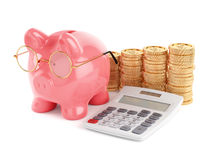 Pink piggy bank with golden coins and calculator Royalty Free Stock Photo