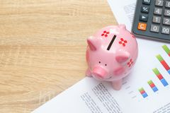 Pink piggy bank with graph and calculator on wooden desk - growi. Ng interest rate concept Stock Photo