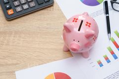 Pink piggy bank with graph and calculator on wooden desk - growi. Ng interest rate concept Stock Images