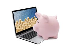 Piggy bank and laptop with stacks of golden coins on white background royalty free stock image