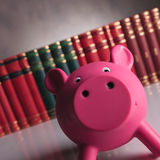 Pink piggy bank looking happy in front of book Royalty Free Stock Image