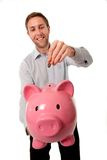 Pink piggy bank with man inserting coins into it. Stock Photos