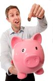 Pink piggy bank with man inserting coins into it. Stock Photo