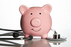 Pink piggy bank with medical stethoscope. On white concept for financial checkup or saving for medical insurance costs Stock Images