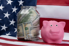 Pink piggy bank and money in the bank on the background of the flag. Pink piggy bank and money in the bank on the background Stock Image