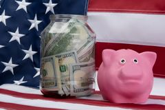 Pink piggy bank and money in the bank on the background of the flag. Pink piggy bank and money in the bank on the background Royalty Free Stock Image