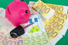 Pink piggy bank with money, car key. A pink piggy bank with money, car key Royalty Free Stock Photography