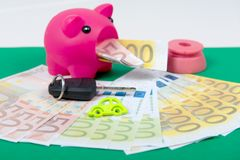 Pink piggy bank with money, car key on a green carpet. A pink piggy bank with money, car key on a green carpet Stock Photography