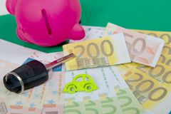 Pink piggy bank with money, car key on a green carpet. A pink piggy bank with money, car key on a green carpet Stock Photos