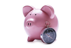 Pink piggy bank next to a vintage compass Stock Photography