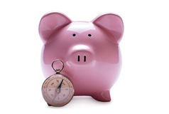 Pink piggy bank next to a vintage compass Stock Photos