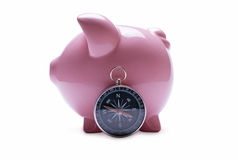 Pink piggy bank next to a vintage compass Royalty Free Stock Photos