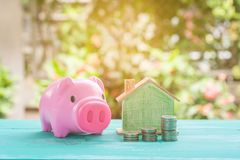 Pink piggy bank over coins stack, saving money Royalty Free Stock Photos