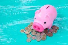 pink piggy bank over coins stack, saving money Stock Photos