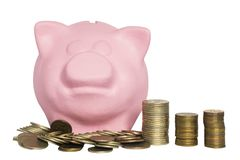 Pink piggy bank and a pile of coins in front of it on a white background stock photos