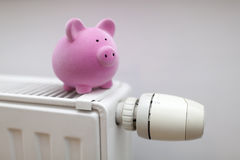 Pink piggy bank on radiator Royalty Free Stock Photography