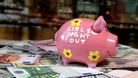 Pink piggy bank on rotating surface with dollars and euro banknotes stock video