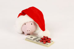 Pink piggy bank with Santa Claus hat and stack of money american hundred dollar bills with red bow Stock Image