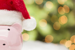 Pink Piggy Bank with Santa Hat on Snowflakes Royalty Free Stock Images