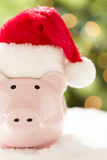 Pink Piggy Bank with Santa Hat on Snowflakes. Pink Piggy Bank Wearing Red and White Santa Hat on Snowflakes with Abstract Green and Golden Background Stock Images