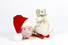 Pink piggy bank with Santas hat and glasses standing next to red sled with Santas bag and stack of money american hundred dollar b Royalty Free Stock Images