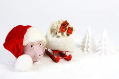 Pink piggy bank with Santas hat with pompom  and glasses standing next to red sled with Santas bag with  three gifts with gold bow Stock Photo