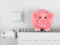 Pink piggy bank saving electricity and heating costs. Close up Royalty Free Stock Images