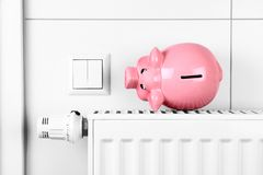 Pink piggy bank saving heating and electricity costs. Top view Stock Photos