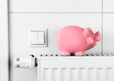 Pink piggy bank saving not electricity and heating costs. Close up Royalty Free Stock Image