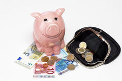 Pink piggy bank with savings on white background Royalty Free Stock Photo