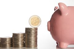 Pink piggy bank and stack of coins growing up with two euro coin Stock Images