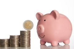 Pink piggy bank and stack of coins growing up with two euro coin royalty free stock images