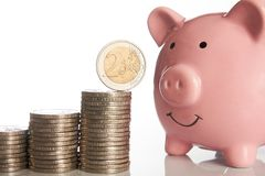 Pink piggy bank and stack of coins growing up with two euro coin Royalty Free Stock Photo