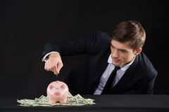 Pink piggy bank standing on dollars. Royalty Free Stock Photos