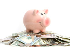 Pink piggy bank standing on a pile of coins and bills, suggesting money savings concept. Pink piggy bank standing on piled up money, suggesting money savings Stock Photos