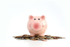 Pink piggy bank standing on a pile of coins and bills, suggesting money savings concept Stock Photos
