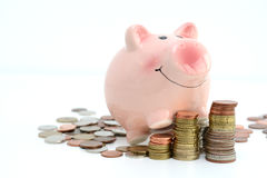 Pink piggy bank standing on a pile of coins and bills, suggesting money savings concept Stock Images