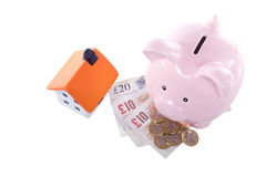 Pink piggy bank with sterling cash and model home Stock Image
