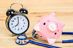 Pink piggy bank with stethoscope. Pink piggy bank with stethoscope and alarm clock on wooden background Royalty Free Stock Photography