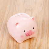 Pink piggy bank on table Stock Image