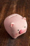 Pink piggy bank on a table Royalty Free Stock Images